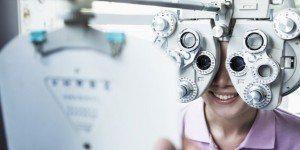 Close-up of optometrist doing an eye exam on young woman